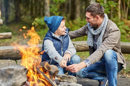 father and son: camping, tourism, hike, family and people concept - happy father and son roasting marshmallow over campfire