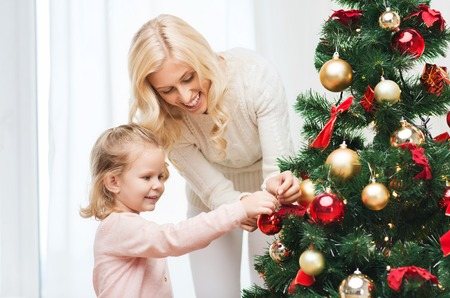 home decorating: family, x-mas, winter holidays and people concept - happy mother and little daughter decorating christmas tree at home