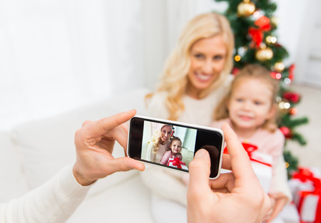 family picture: family, christmas, technology and people concept - close up of man taking picture of his family by smatrphone