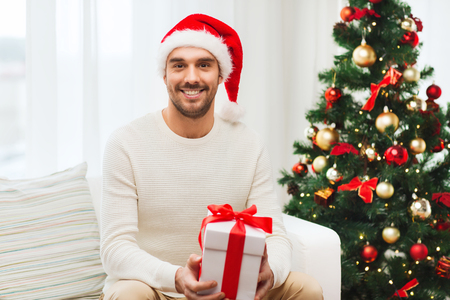 christmas hat: christmas, holidays and people concept - happy man in santa hat with gift box at home