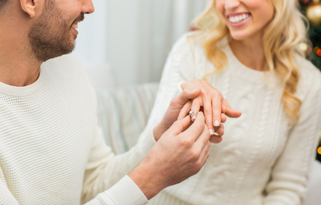 love, couple, relationship and holidays concept - happy man giving diamond ring to woman for christmas Foto de archivo
