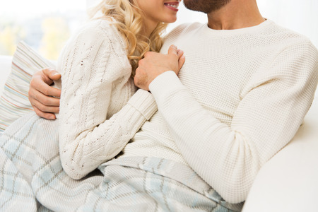love, family, winter and happiness concept - close up of happy couple cuddling under paid at home