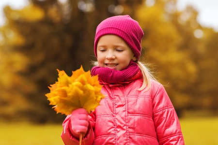 autumn, childhood, happiness and people concept - happy beautiful little girl with maple leaves bunch outdoors