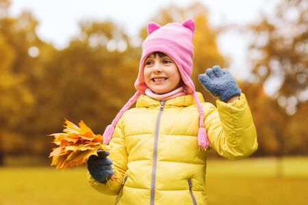 beautiful preteen girl: autumn, childhood, happiness and people concept - happy beautiful little girl with maple leaves bunch waving hand outdoors
