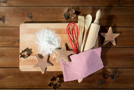 christmas cooking: baking, cooking, christmas and food concept - close up of gingerbread cookies, molds with flour and kitchenware set on wooden cutting board at home kitchen from top Stock Photo