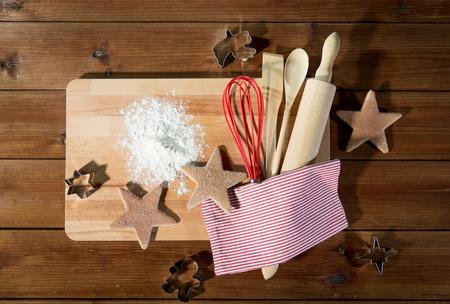 ustensiles de cuisine: cuisson, noël et concept de restauration - gros plan de biscuits au gingembre, des moules avec de la farine et des ustensiles de cuisine situé sur une planche à découper en bois à la maison cuisine de haut