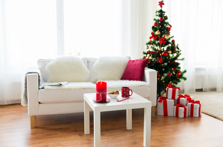 living room: christmas, holidays, winter, home and still life concept - living room interior with christmas tree and gifts Stock Photo