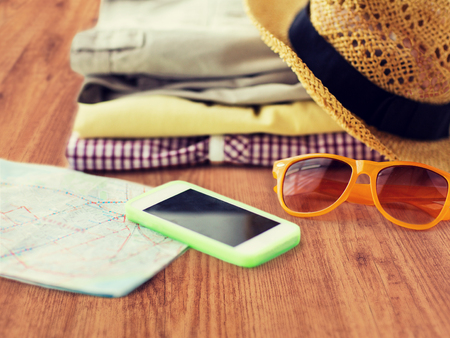 folded clothes: travel, summer vacation, tourism and objects concept - close up of folded clothes, smartphone and touristic map on wooden floor Stock Photo