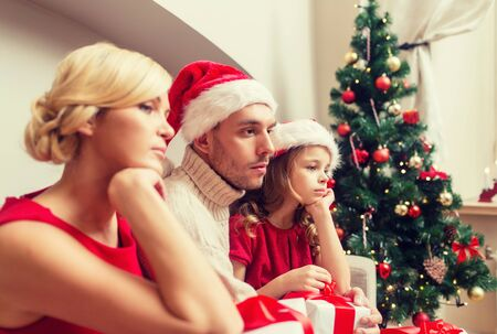 sad little girl: family, christmas, x-mas, winter and people concept - unhappy family at home with many gift boxes
