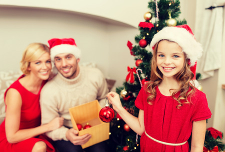 decorating christmas tree: family, christmas, x-mas, winter, happiness and people concept - smiling family in santa helper hats decorating christmas tree
