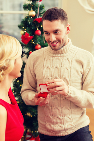 proposing: love, couple, christmas, x-mas, winter, relationship and dating concept - romantic man proposing to a woman in red dress
