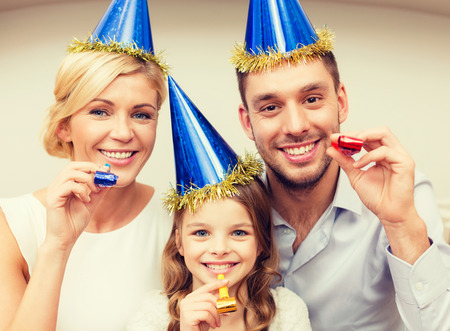 favor: celebration, family, holidays and birthday concept - three smiling women wearing blue hats and blowing favor horns