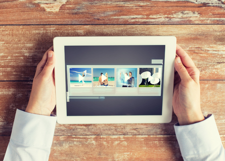 slideshow: people, multimedia and technology concept - close up of hands with video gallery slideshow on tablet pc at table Stock Photo