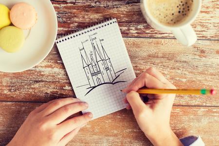 dibujo: la creatividad, la imaginación, la inspiración y el concepto de la gente - cerca de las manos femeninas de dibujo con el lápiz en el cuaderno, café y galletas en la mesa