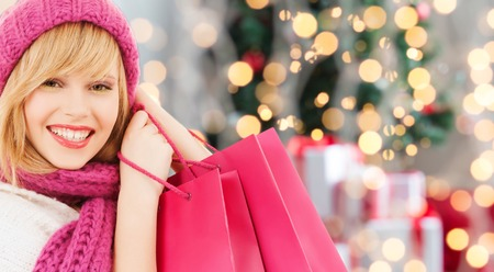 christmas shopping bag: happiness, winter holidays and people concept - smiling young woman in hat and scarf with pink shopping bags over christmas tree background Stock Photo