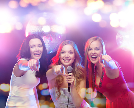 karaoke singer: party, holidays, nightlife, entertainment and people concept - concept - happy women with microphone singing karaoke and pointing finger on you at night club Stock Photo