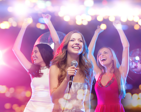 people singing: party, holidays, nightlife, entertainment and people concept - concept - happy women with microphone singing karaoke and dancing at night club Stock Photo