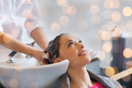 beauty, hair care and people concept - happy young woman with hairdresser washing head at hair salon over holidays lights Zdjęcie Seryjne - 49526065