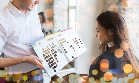 dyeing: beauty, hair dyeing and people concept - happy young woman with hairdresser choosing hair color from palette samples at salon over holidays lights Stock Photo