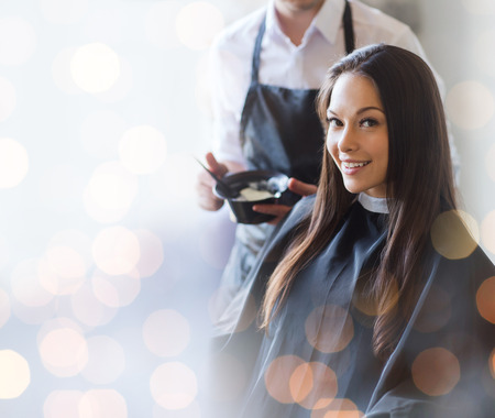 dyeing: beauty and people concept - happy young woman with hairdresser coloring hair at salon
