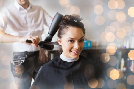 hairdressing: beauty, hairstyle and people concept - happy young woman and hairdresser with fan making hot styling at hair salon over holidays lights Stock Photo