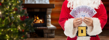 christmas profits: christmas, holidays, winning, currency and people concept - close up of santa claus holding euro money over living room with fireplace and christmas tree background