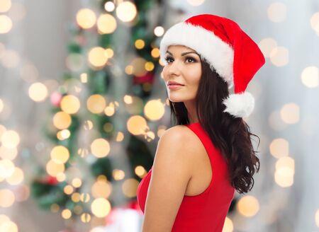 navidad elegante: personas, días de fiesta, la Navidad y la celebración de concepto - mujer atractiva en el sombrero de santa y el vestido rojo sobre fondo de las luces Foto de archivo