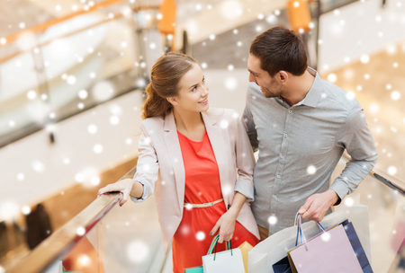 sale, consumerism and people concept - happy young couple with shopping bags rising on escalator and talking and raising on escalator in mall with snow effect Stock Photo