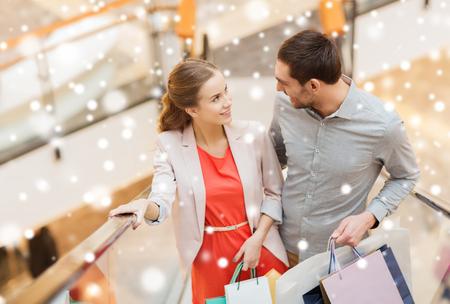 centro comercial: venta, el consumismo y el concepto de la gente - joven pareja feliz con bolsas de la compra subiendo en la escalera móvil y hablando y elevando en las escaleras mecánicas en el centro comercial con efecto de nieve