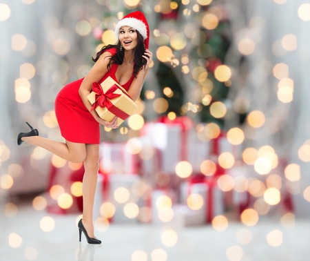 xmas tree: people, holidays, christmas and celebration concept - beautiful sexy woman in red dress and santa hat with gift box listening to something over christmas tree lights and presents background Stock Photo
