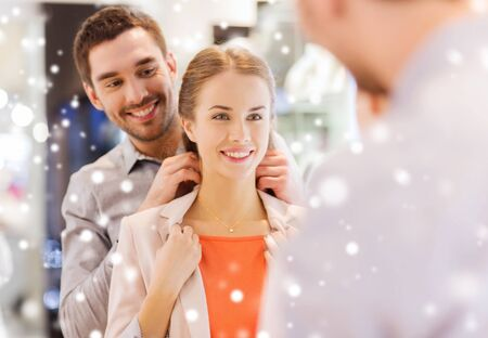 trying on: sale, consumerism, presents, holidays and people concept - happy couple trying golden pendant on at jewelry store in mall with snow effect Stock Photo