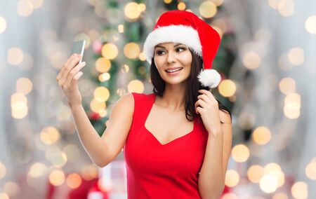 sexy christmas: people, holidays, christmas and technology concept - beautiful sexy woman in red santa hat taking selfie picture by smartphone over christmas tree lights and presents background