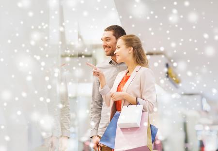 mujeres elegantes: venta, el consumismo y el concepto de la gente - joven pareja feliz con bolsas de la compra que señala el dedo a la ventana de la tienda en centro comercial con efecto de nieve Foto de archivo