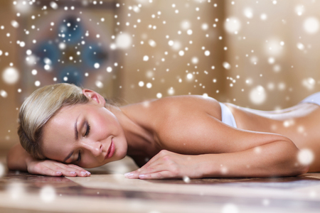 woman bath: people, beauty, spa, healthy lifestyle and relaxation concept - beautiful young woman lying on hammam table in turkish bath with snow effect