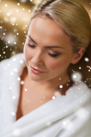 bath robe: people, beauty, healthy lifestyle and relaxation concept - close up of beautiful young woman resting on chair in bath robe at spa with snow effect