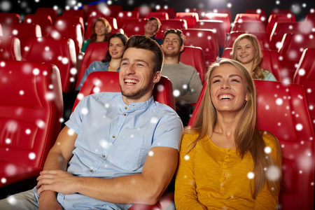 christmas movies: cinema, entertainment and people concept - happy couple watching comedy and laughing in movie theater over snowflakes