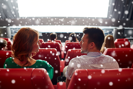 family movies: cinema, entertainment and people concept - happy friends or couple watching movie in theater on last row and talking from back over snowflakes