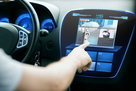 transport, modern technology, mass media and people concept - male hand pointing finger to monitor on car panel and reading news Stockfoto