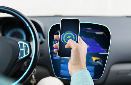mode transport: transport, business trip, technology and people concept - close up of man driving car and setting eco mode on smartphone and and navigator on board computer