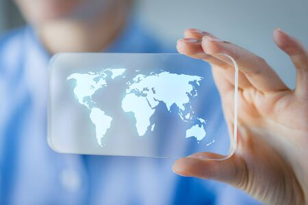 transparent system: business, technology, international communication, mass media and people concept - close up of woman hand holding and showing transparent smartphone with world map on screen