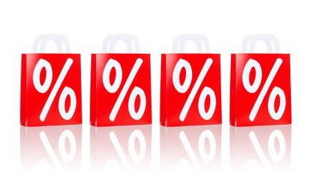 consumerism: sale, consumerism, discount, advertisement and retail concept - many red shopping bags with percentage sign Stock Photo
