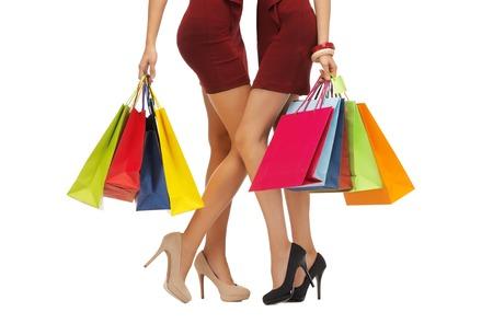 tacones rojos: las personas, la venta y el concepto de descuento - cerca de las mujeres en faldas cortas de color rojo y zapatos de tacón alto con bolsas de la compra