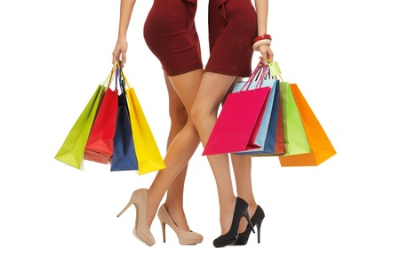 high up: people, sale and discount concept - close up of women in red short skirts and high heeled shoes with shopping bags