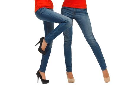 in jeans: concepto de la gente, la moda, el estilo y la ropa - cerca de dos piernas de las mujeres en pantalones vaqueros