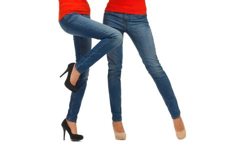 red jeans: people, fashion, style and clothing concept - close up of two women legs in jeans