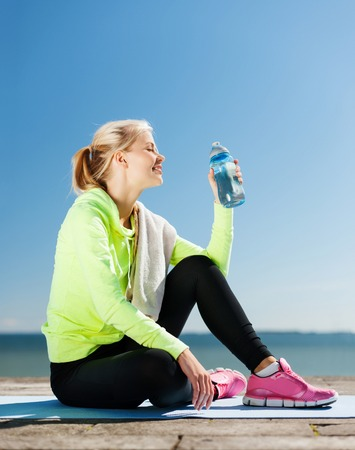 water sports: sport and lifestyle concept - woman drinking water after doing sports outdoors