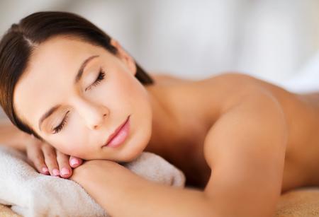 schoonheid: gezondheid en schoonheid, complex en ontspanning concept - mooie vrouw met gesloten ogen in spa salon liggend op de massage bureau Stockfoto