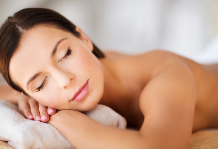 beauté: la santé et la beauté, station et de détente notion - belle femme avec les yeux fermés dans un salon de spa se trouvant sur le bureau de massage