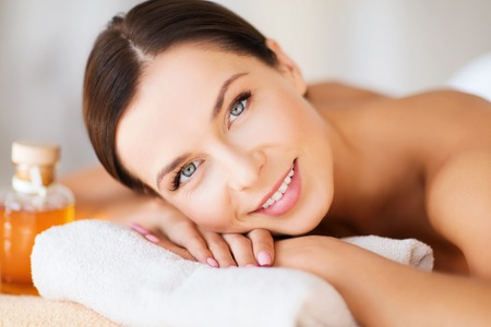 nice body: beauty and spa concept - happy woman in spa salon lying on the massage desk Stock Photo