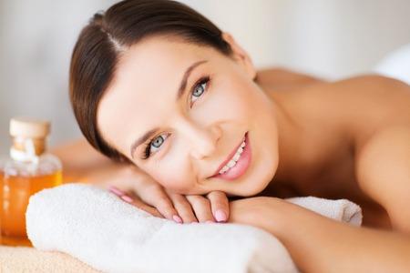 tratamientos corporales: belleza y spa concepto - mujer feliz en el salón de spa acostado sobre la mesa de masaje